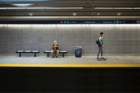 Man watching skateboarder subway station platform