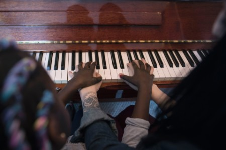 Overhead view mother teaching daughter piano lesson