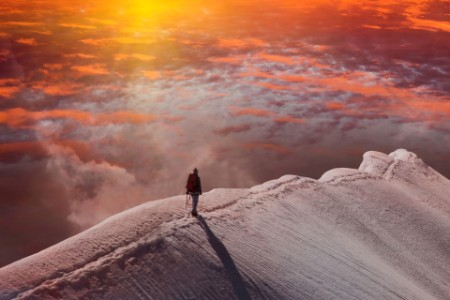 person on mountain at sunset