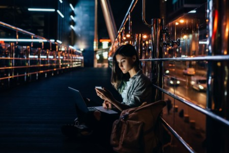 Side view of young woman with laptop using smartphone with night city on background