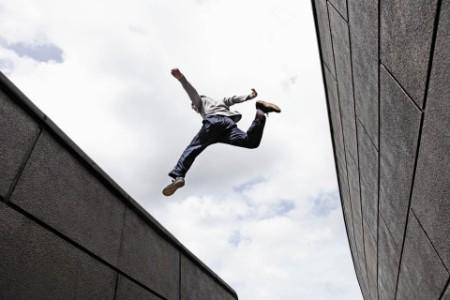 Teenage boy jumping over gap between walls