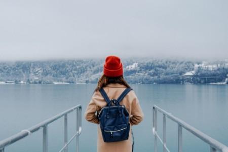 Woman looking foggy lake winter