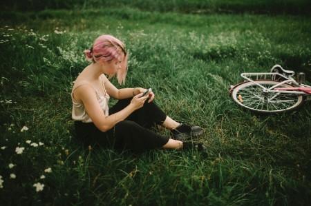 Woman sitting field checking smart phone