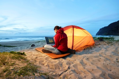 A woman with laptop by tent
