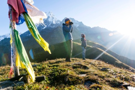 Couple on the hill with binoculars and prayer flags