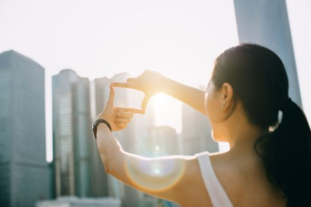 Young woman frames the city skyline into a finger frame