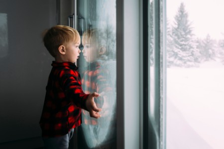 Boy looking through window home winter