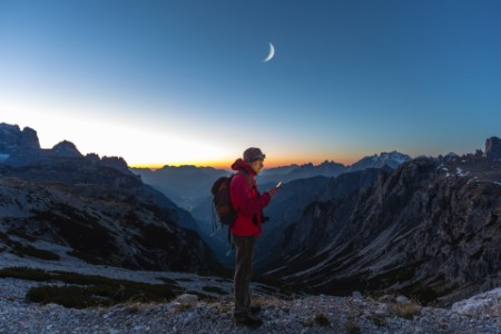 Excursionista mirando un mapa en su dispositivo móvil, montañas, atardecer
