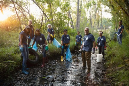 people volunteering cleaning garbage stream