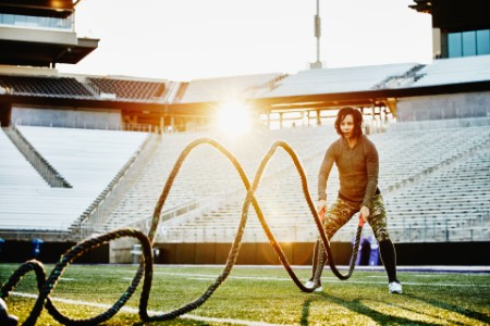 Athlete working out battle rope stadium