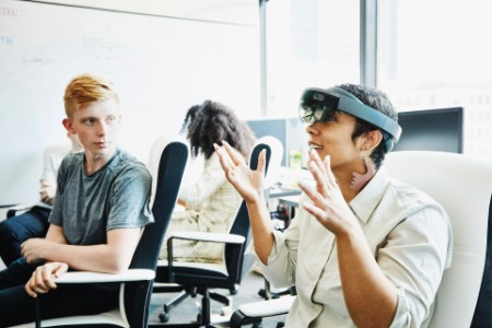 Female engineer discussion coworker testing augmented reality headset
