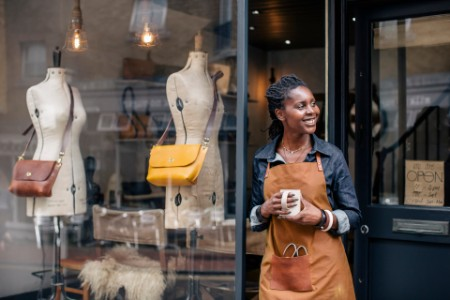 A small business owner stands outside her handbag shop