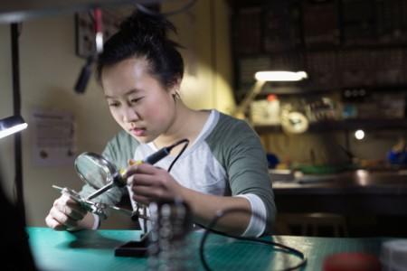 Kvindelig elektronikingeniør lodder