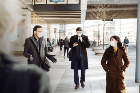 business colleagues wearing masks talking on street