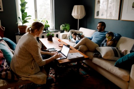 Family using various technologies in living room at home