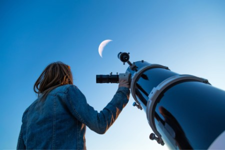 Tax policy young women looking sky through telescope