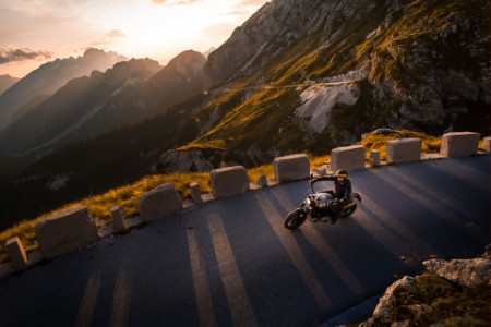 A man riding motorcycle on mountain road, Italy
