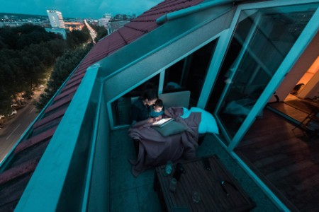 Madre e hijo leyendo cuentos en la noche desde una tablet en el balcón