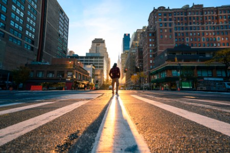 One person crossing a junction in manhattan at sunrise new york city