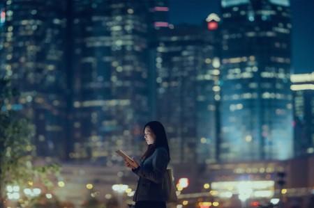 Mulher na cidade à noite em frente aos arranha-céus no seu telemóvel