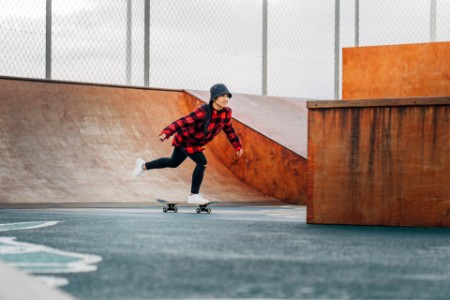 Woman practicing skateboarding amidst ramps