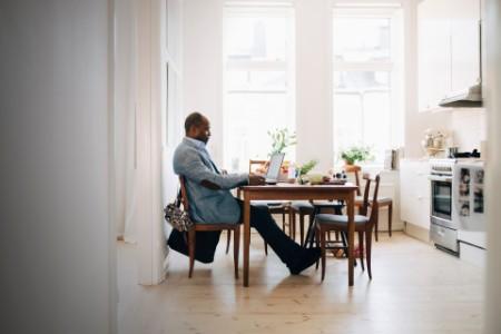 Mann arbeitet am Laptop, während er zu Hause in der Küche sitzt
