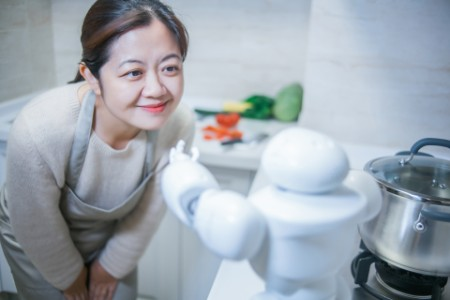 Beautiful woman greeting AI assistant in kitchen