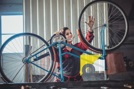 woman fixing a bicycle
