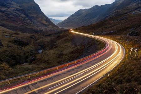 car light trails scenic road mountains Scottish highlands Glencoe dusk