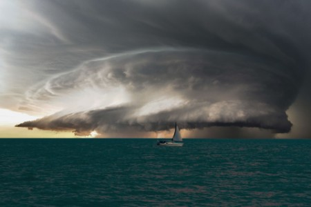 sailing boat on the open sea with storm clouds approaching