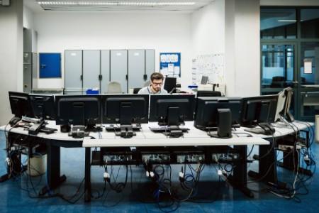 Engineer working behind computers control room