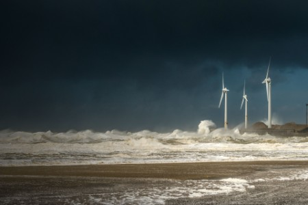 Four wind turbines amidst fierce storm waves and clouds