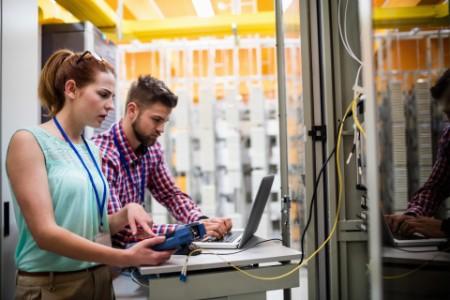 Technicians using laptop in server room