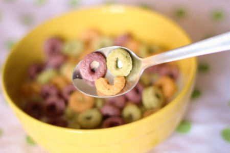 Colored cereal on spoon making happy face