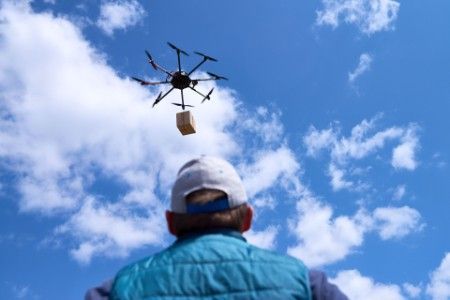 A person checking the drone delivering items
