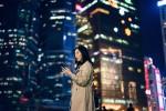Businesswoman using smartphone against cityscape