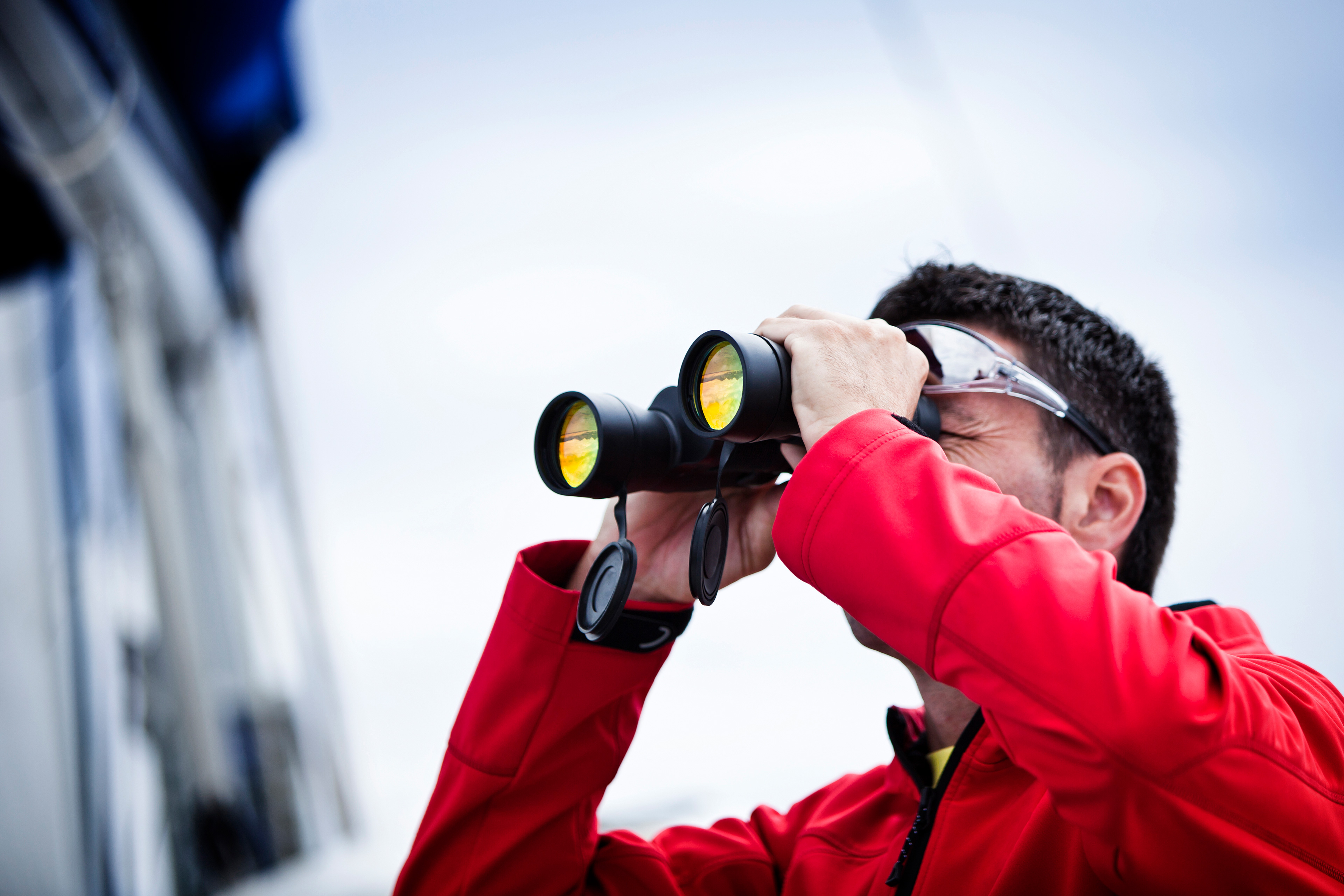 A man looking through binoculars