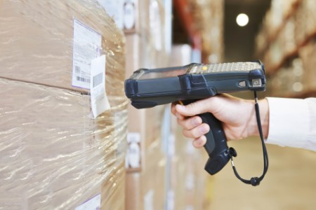 Warehouse worker sealing cardboard boxes