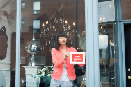 Female business owner displaying help wanted sign in furniture store window