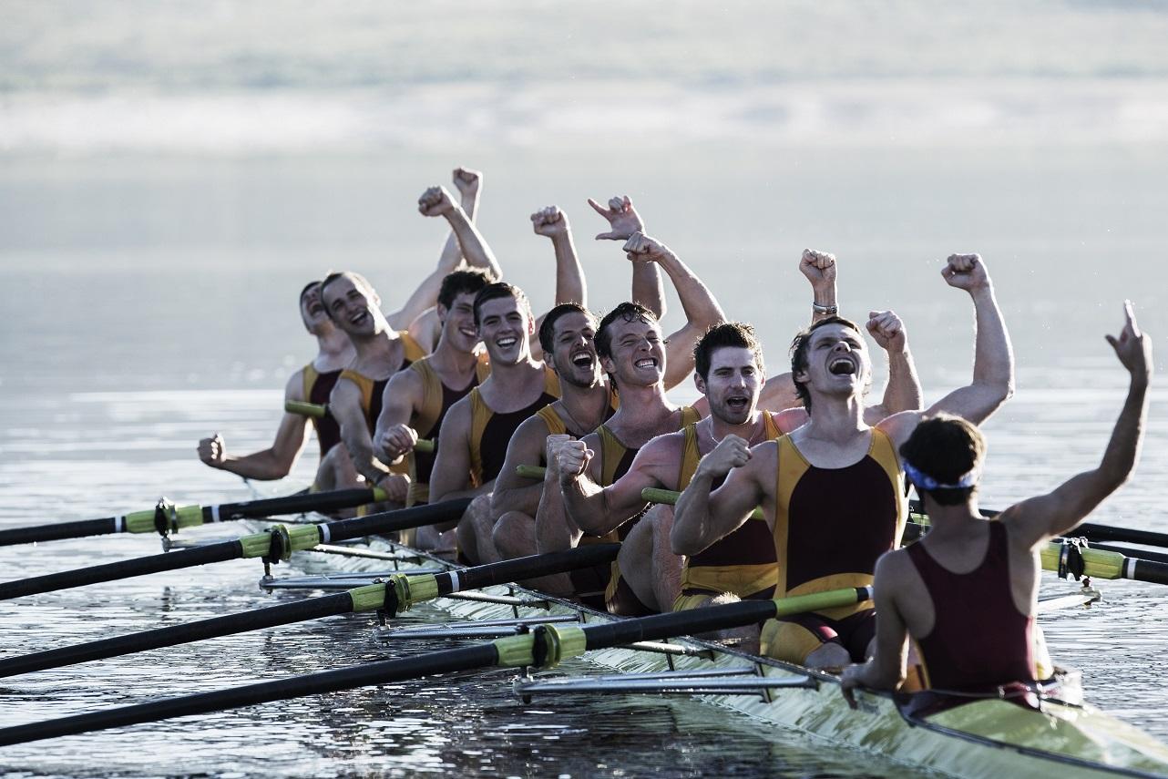 group of men kayaking and cheering