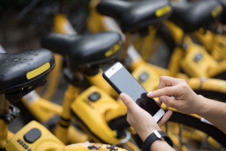 Person using smartphone for bike rental