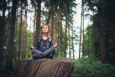 Girl meditating in the woods