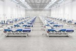 view of rows of hospital beds in a large white room