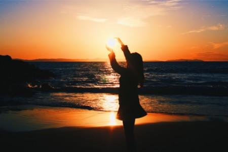 Girl framing sun as it sets