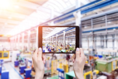 Hands holding tablet up to photograph factory floor