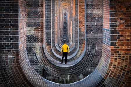 Man in yellow jacket, looking through a viaduct