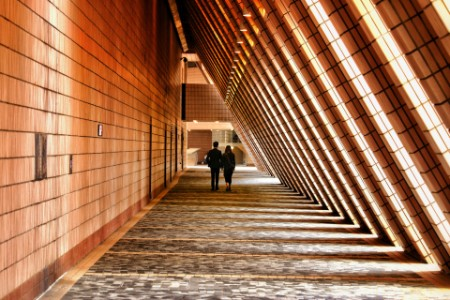 People walking down an architectural corridor