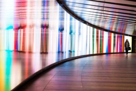 Woman walking down brightly lit corridor