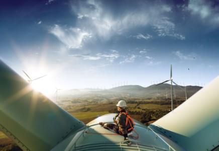 man-sitting-on-wind-turbine