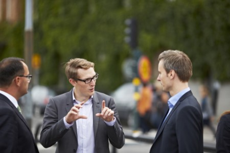 Photo of three businessmen having a conversation in a street